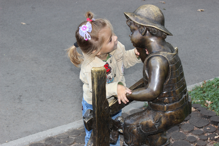 the girl looks at a monument