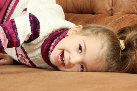 pranks: the amusing cheerful little girl on a sofa