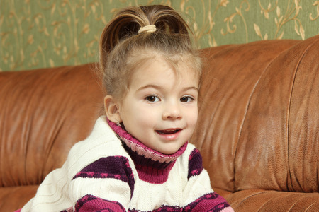 pranks: the amusing cheerful little girl on a sofa