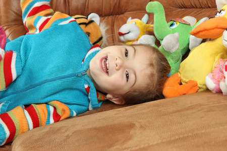 soft toys: the nice little girl on a sofa plays soft toys