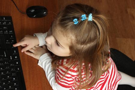 petite fille avec robe: petite fille � l'ordinateur. Clavier et souris d'ordinateur. vue de dessus