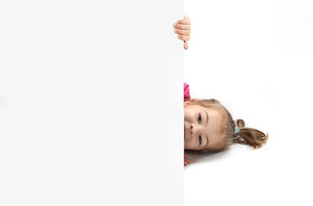 peep out: the little girl looks out because of a sheet of paper. isolate on a white background