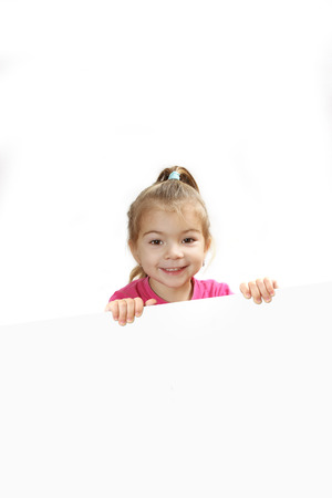 'hide out': the little girl looks out because of a sheet of paper. isolate on a white background