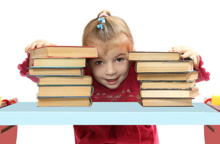 overindulgence: the little girl with books at a table. isolated on a white background