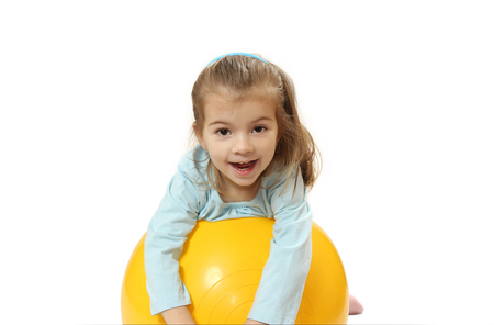 yellow ball: the nice little girl with a big ball. isolated on a white background