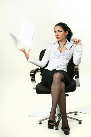 scatters: business woman sitting in a chair scatters paper Stock Photo
