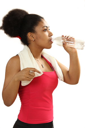 curly headed: black girl drinks water from a bottle. isolate on a white background