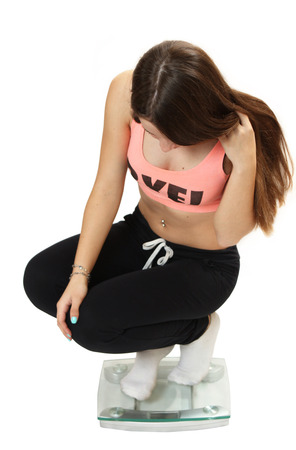 leggings: young sports girl is weighed on scales. isolated on a white background