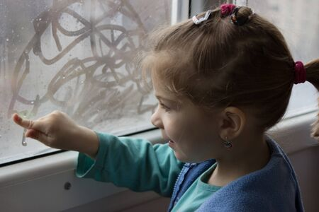 misted: little girl draws a finger on the misted glass Stock Photo