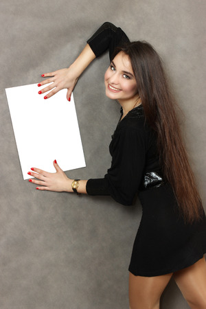 advertize: young nice woman with a white empty sheet of paper. gray background