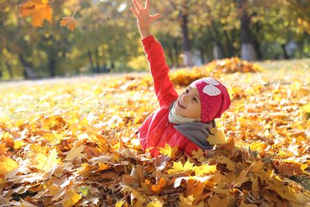 gelukkig klein babymeisje dat in de herfst in gele bladeren speelt Stockfoto