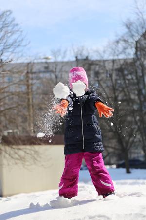 Jeux d'hiver - une petite fille lance une boule de neige