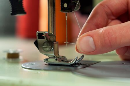 threading: Threading the needle in a sewing machine Stock Photo