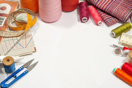 various sewing supplies on a white background with space for text