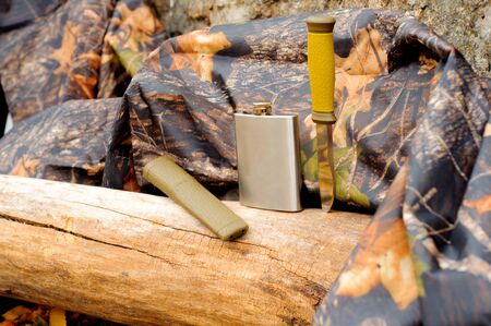Metal flask and a knife on a log next to a raincoat of protective color Stock Photo