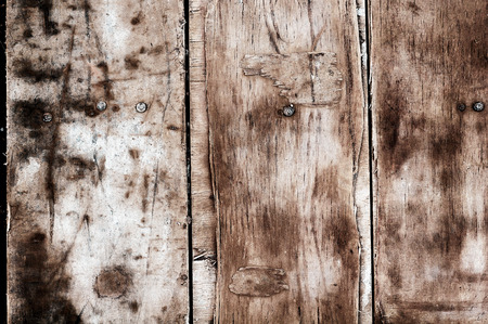 background from old worn dirty wooden boards made of plywood and hammered rusty nails