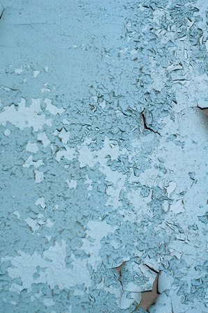 vertical background of old faded blue paint cracked and partially peeled on the wall