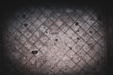 background of old darkened scuffed and scratched gray concrete floor with traces of floor tiles