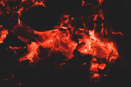 Bright colorful glowing orange-red embers bonfire. Burning fire on black background close-up. Horizontal background.