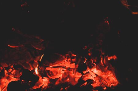Orange red bright colorful embers dying bonfire. Burning fire on black background close-up. Horizontal background. Tree branches dying in fire.