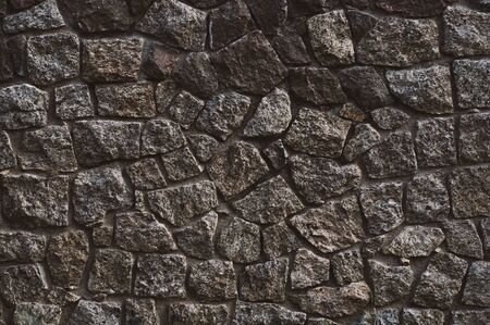 background from a wall erected from roughly treated gray granite stones