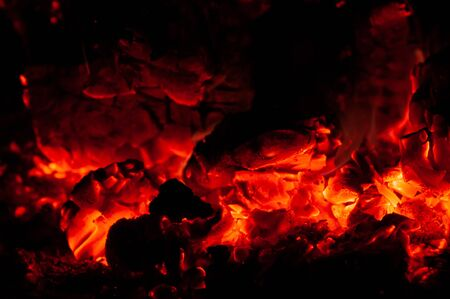 Bright colorful glowing orange-red embers bonfire. Horizontal background. Tree branches dying in fire. Burning fire on black background close-up. 스톡 콘텐츠