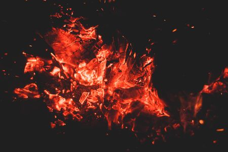 Glowing bright colorful orange-red embers bonfire. Burning coals. Warm bonfire. Horizontal photo. Close-up. Bright fire. Dim fire. Red flame. Dim dark background. 스톡 콘텐츠