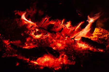 Bright colorful orange-red embers dying bonfire. Horizontal background. Tree branches dying in fire. Burning fire on black background close-up. Stock fotó