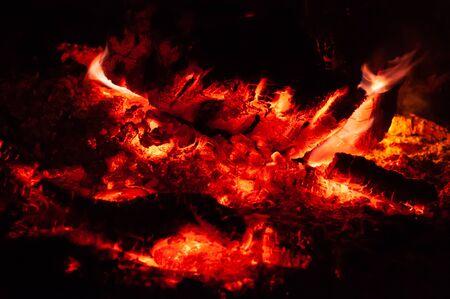 Leuchtend bunte orange-rote Glut sterben am Lagerfeuer. Horizontaler Hintergrund. Äste sterben im Feuer. Brennendes Feuer auf schwarzer Hintergrundnahaufnahme. Standard-Bild