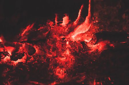 Fading cozy bonfire with calving bright coals. Burning fire on black background close-up. Horizontal background. Tree branches dying in fire