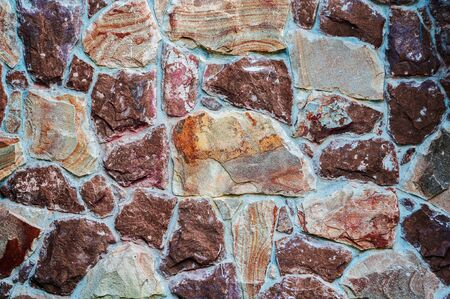 background from a wall erected from roughly treated brown and gray granite stones.