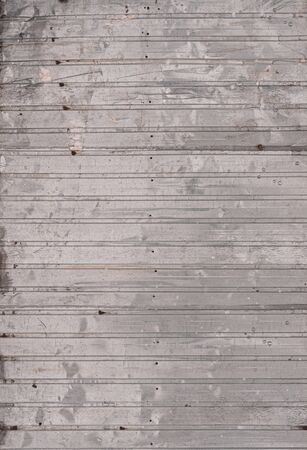 Old corrugated galvanized sheet as background. Vertical metal texture background. Surface of metal sheet as decorative element. Outdoors. Close-up. Facade premises. Fencing site territory garden. 스톡 콘텐츠