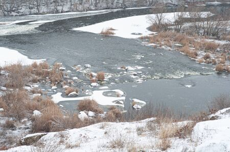 First snow fell on dry yellow grass on banks of river. River flows along hilly snow-covered shore. Beautiful winter landscape. Bank of river after first snowfall. Cloudy winter day. Horizontal photo