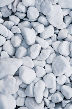 Background from rounded beautiful white pebbles. Sea pebbles. Natural stone texture. Riverbank. Beach. Decorative element. Design flower beds garden paths. Vertical photo. Close-up.