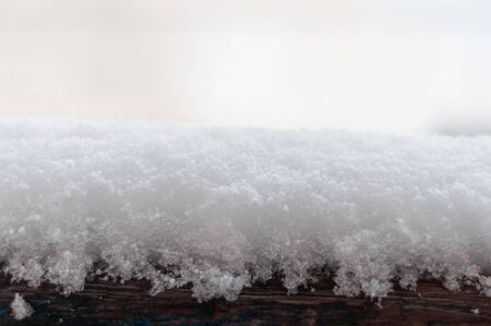 Texture of white fluffy snow on wooden surface. White cold snow and natural brown wood. Contrast. Blurred background. Close-up. Snow grains on wooden surface. Elements of winter. Horizontal photo.