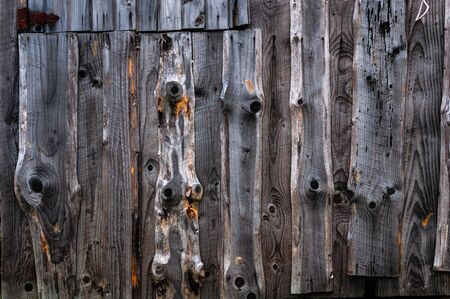 A wall made of old, darkened, frayed gray wooden knotty planks.
