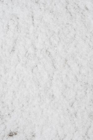 Fluffy snow covered frozen ground with thin layer. Seamless texture of soft fluffy snowflakes. Background. Fresh clean shining snow. Close-up. Winter landscape. Vertical photo. Outdoors. Reklamní fotografie