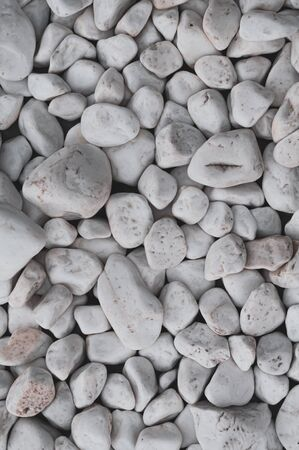 Background rounded polished white smooth stones. Decorative beautiful white pebbles. Various textures. Riverbank. Beach. Outdoors. Marble pebbles. Small river stones. Close-up. Vertical photo. Reklamní fotografie