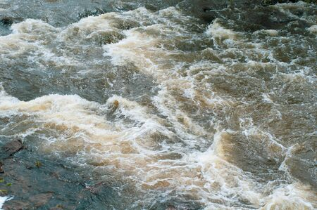 Background, top view, fast flowing river with dark blue-brown water and white foam waves