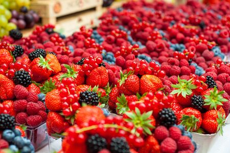 Sale juicy, fresh strawberries, raspberries and blackberries in market square, Prague, Czech Republic. Nutritious healthy berry diet food. Berries close up. Stock Photo