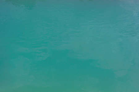 Background close-up, turquoise green water surface lake, outdoors, horizontal photo.