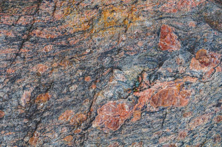 Background with natural rough granite stone, solid colorful texture. Close-up photo. Nature, outdoors. Horizontal photo
