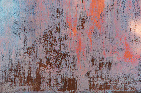 Rusty metal background with old red peeling cracked paint, atmospheric impact, outdoors, horizontal photo. Close-up.