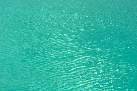 Bright, colorful background close up, turquoise green water surface of the lake, outdoors, horizontal photo.