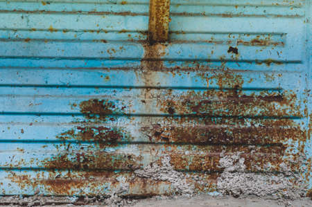 Bright colorful background from rusty metal with old blue shabby cracked paint, atmospheric impact, outdoors, horizontal photo, close-up.