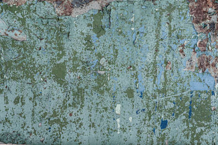 Concrete wall background with old, blue and green peeling cracked paint, atmospheric impact, outdoors, horizontal close-up photo.