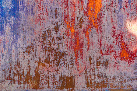 Bright colorful background from rusty metal with old blue and red shabby cracked paint, atmospheric impact, outdoors, horizontal photo. Close-up. Stock Photo
