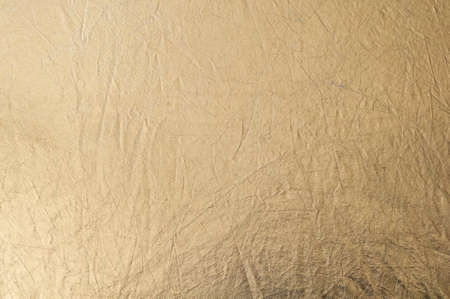 Gold texture, fabric reflector, simple stretched gold background, horizontal photo.