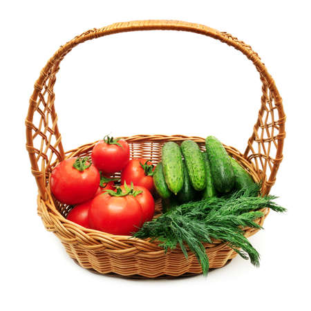 Tomatoes and cucumbers in a basket isolated on a white background. photo