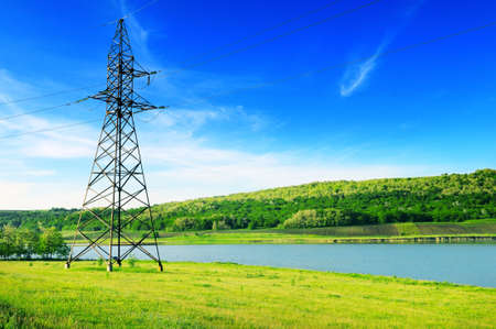 electrical tower: High-voltage power line on the shore of the lake.                                     Stock Photo